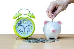 Τράπεζα Piggy με το νόμισμα και ξυπνητήρι στο ξύλινο επιτραπέζιο υπόβαθρο Στοκ φωτογραφία με δικαίωμα ελεύθερης χρήσης