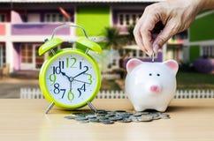 Τράπεζα Piggy με το νόμισμα και ξυπνητήρι στο ξύλινο επιτραπέζιο υπόβαθρο Στοκ Εικόνα