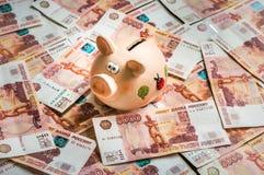Τράπεζα Piggy σε έναν σωρό ρωσικών πέντε χιλιάες τραπεζογραμματίων Στοκ φωτογραφία με δικαίωμα ελεύθερης χρήσης