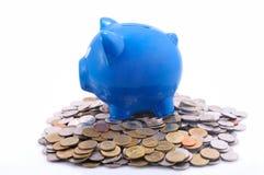 Τράπεζα Piggy σε έναν σωρό των νομισμάτων Στοκ Εικόνες