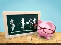 Τράπεζα Piggy στα γυαλιά και τον πίνακα επάνω Στοκ εικόνα με δικαίωμα ελεύθερης χρήσης