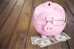 Τράπεζα Piggy στα γυαλιά και χρήματα σε ξύλινο Στοκ Εικόνα