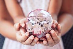 Τράπεζα Piggy στα χέρια παιδιών και μητέρων παιδιών στοκ φωτογραφία