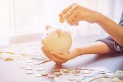 Τράπεζα Piggy υπό εξέταση με το σωρό μετρητών Στοκ Εικόνες