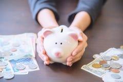 Τράπεζα Piggy υπό εξέταση με το σωρό μετρητών Στοκ φωτογραφία με δικαίωμα ελεύθερης χρήσης