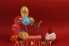 Τράπεζα Piggy, χρόνια πολλά, καπέλο κομμάτων και πολύχρωμα μπαλόνια κομμάτων στο κόκκινο υπόβαθρο Στοκ Εικόνα