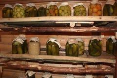 Τράπεζες με τα αγγούρια τουρσιών, ντομάτες, λάχανο στην αποθήκευση στοκ εικόνες