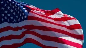 Τρέμοντας ΑΜΕΡΙΚΑΝΙΚΗ σημαία στο υπόβαθρο μπλε ουρανού φιλμ μικρού μήκους