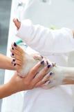 Τρέφοντας moisturizer πόδια γυναικών μασκών Aplying Στοκ Φωτογραφία