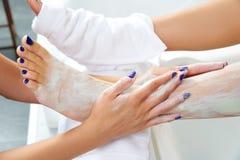 Τρέφοντας moisturizer πόδια γυναικών μασκών Aplying Στοκ Εικόνες