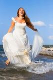 Τρέχοντας γελώντας νύφη στη θάλασσα Στοκ Εικόνες