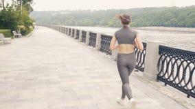 Τρέχοντας γυναίκα στο ανάχωμα πόλεων κατά τη διάρκεια της κατάρτισης πρωινού υπαίθριας απόθεμα βίντεο