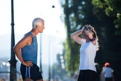 Τρέχοντας διαδρομή προγραμματισμού ζευγών Jogging και θέτοντας μουσική Στοκ φωτογραφία με δικαίωμα ελεύθερης χρήσης