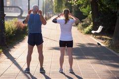 Τρέχοντας διαδρομή προγραμματισμού ζευγών Jogging και θέτοντας μουσική Στοκ Φωτογραφίες