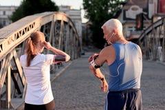 Τρέχοντας διαδρομή προγραμματισμού ζευγών Jogging και θέτοντας μουσική Στοκ Εικόνες