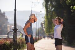 Τρέχοντας διαδρομή προγραμματισμού ζευγών Jogging και θέτοντας μουσική Στοκ εικόνα με δικαίωμα ελεύθερης χρήσης