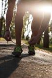 Τρέχοντας κινηματογράφηση σε πρώτο πλάνο ατόμων του τρεξίματος των παπουτσιών στο ηλιοβασίλεμα ή την ανατολή Πόδια δρομέων Στοκ Φωτογραφία