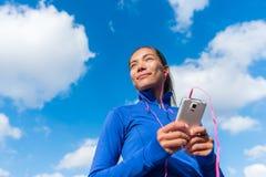 Τρέχοντας κορίτσι που ακούει τη μουσική στο έξυπνο τηλέφωνο Στοκ φωτογραφία με δικαίωμα ελεύθερης χρήσης