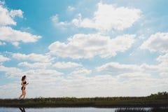 Τρέχοντας κορίτσι σε έναν πράσινο τομέα και έναν φωτεινό ουρανό στοκ φωτογραφία με δικαίωμα ελεύθερης χρήσης