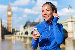 Τρέχοντας κορίτσι του Λονδίνου που ακούει τη μουσική smartphone Στοκ Εικόνα