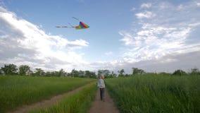 Τρέχοντας μικρό παιδί στα παιχνίδια καπέλων και πουκάμισων με τον πετώντας ικτίνο στον πράσινο τομέα στο υπόβαθρο του ουρανού, ευ απόθεμα βίντεο