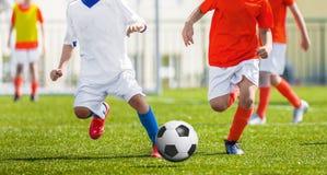 Τρέχοντας νέοι ποδοσφαιριστές ποδοσφαίρου Ποδοσφαιριστές που κλωτσούν τη σφαίρα ποδοσφαίρου Στοκ εικόνες με δικαίωμα ελεύθερης χρήσης