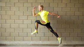 Τρέχοντας νεαρός άνδρας, γκρίζος τοίχος στο υπόβαθρο στοκ εικόνα
