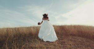 Τρέχοντας νύφη στο καταπληκτικό μακρύ φόρεμα μέσω του τοπίου απόθεμα βίντεο