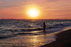 Τρέχοντας παιδί στην παραλία σε ένα όμορφο κόκκινο ηλιοβασίλεμα στοκ εικόνα