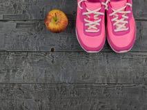 Τρέχοντας παπούτσια γυναικών ` s ζευγαριού ρόδινα για την ικανότητα και η κόκκινη Apple στο ξύλινο πάτωμα κορυφαία όψη Στοκ φωτογραφίες με δικαίωμα ελεύθερης χρήσης