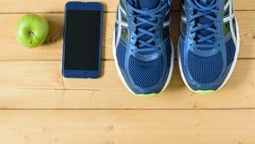 Τρέχοντας παπούτσια, Apple και τηλέφωνο στο ξύλινο πάτωμα κορυφαία όψη Επίπεδος βάλτε Στοκ φωτογραφία με δικαίωμα ελεύθερης χρήσης