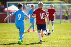 Τρέχοντας ποδοσφαιριστές ποδοσφαίρου Ποδοσφαιριστές που κλωτσούν τον αγώνα ποδοσφαίρου Σχολικά πρωταθλήματα ποδοσφαίρου Στοκ φωτογραφίες με δικαίωμα ελεύθερης χρήσης
