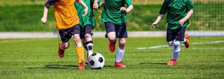 Τρέχοντας ποδοσφαιριστές νεολαίας Παιδιά που παίζουν το παιχνίδι ποδοσφαίρου ποδοσφαίρου Στοκ φωτογραφία με δικαίωμα ελεύθερης χρήσης