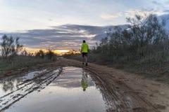 Τρέχοντας στον τομέα στο ηλιοβασίλεμα στα σορτς, με τα πάνινα παπούτσια στοκ εικόνα με δικαίωμα ελεύθερης χρήσης