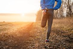 Τρέχοντας τέντωμα - γυναίκα που κάνει τις ασκήσεις προτού να τρέξετε στοκ φωτογραφία