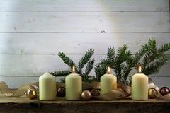Τρία άσπρα καίγοντας κεριά στην τρίτη εμφάνιση, ντεκόρ Χριστουγέννων Στοκ Εικόνες