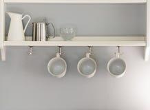 Τρία άσπρα φλυτζάνια καφέ που κρεμούν σε μια σειρά συνεδρίαση κανατών και γυαλιού Στοκ Φωτογραφία