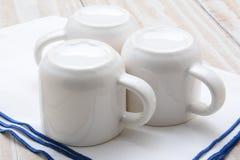 Τρία άσπρα φλυτζάνια στην πετσέτα φραγμών Στοκ φωτογραφία με δικαίωμα ελεύθερης χρήσης