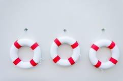Τρία άσπρο κόκκινο Lifebuoy με έναν πίνακα στον άσπρο τοίχο Στοκ φωτογραφίες με δικαίωμα ελεύθερης χρήσης