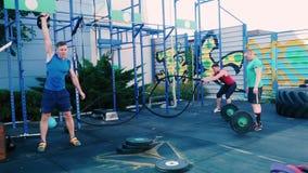 Τρία άτομα που εκπαιδεύουν σκληρά στο χώρο αθλήσεων απόθεμα βίντεο