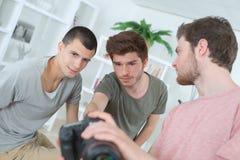 Τρία άτομα που εξετάζουν τη φωτογραφία στην επίδειξη καμερών στοκ φωτογραφίες με δικαίωμα ελεύθερης χρήσης
