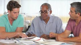 Τρία άτομα που διοργανώνουν τη συνεδρίαση στο δημιουργικό γραφείο απόθεμα βίντεο