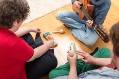 Τρία άτομα που παίζουν τα διάφορα όργανα στοκ φωτογραφία με δικαίωμα ελεύθερης χρήσης