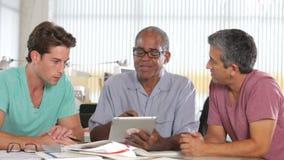 Τρία άτομα που χρησιμοποιούν τον υπολογιστή ταμπλετών στο δημιουργικό γραφείο φιλμ μικρού μήκους