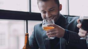 Τρία άτομα ψήνουν με τις κούπες της μπύρας, χαμόγελο ο ένας στον άλλο και το πίνουν Ευτυχής μαζί, φίλοι για πάντα αρσενικό απόθεμα βίντεο