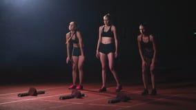 Τρία αθλητικά κορίτσια στα μαύρα ενδύματα του αθλητή τη νύχτα treadmill θα αρχίσουν για τον αγώνα στην ορμή φιλμ μικρού μήκους