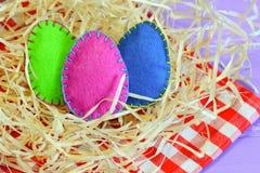 Τρία αισθάνθηκαν τα αυγά των διάφορων χρωμάτων Εύκολο και απλό αισθητό ντεκόρ αυγών compisition Πάσχα Κεντρικά τεμάχια επιτραπέζι Στοκ Εικόνες
