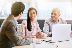 Τρία ανώτατα στελέχη επιχείρησης που επικοινωνούν κατά τη διάρκεια της συνεδρίασης στη αίθουσα συνδιαλέξεων στοκ φωτογραφία