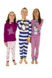 Τρία λατρευτά παιδιά που φορούν το ζωηρόχρωμο χασμουρητό χειμερινών πυτζαμών στοκ φωτογραφία