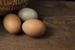 Τρία αυγά και ένα ψάθινο καλάθι στοκ εικόνα με δικαίωμα ελεύθερης χρήσης